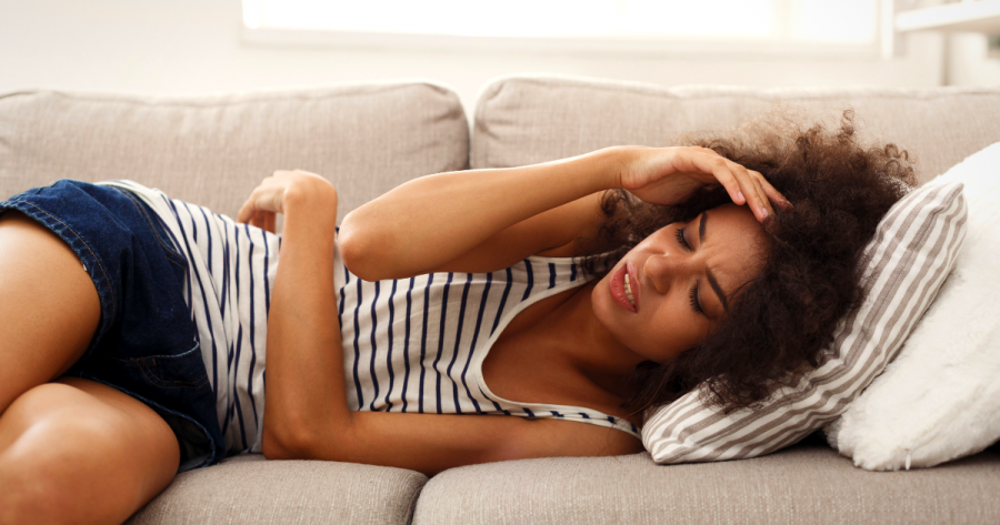 Woman laying down, looking uncomfortable and in pain